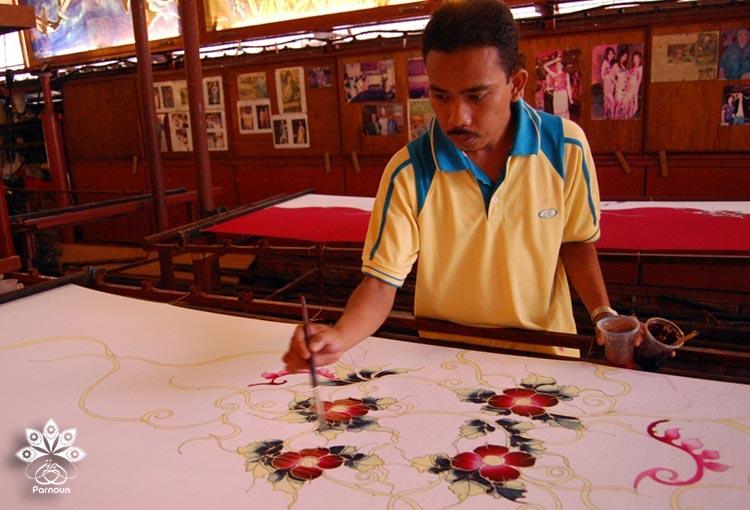 هنرمند مالزیایی در حال ایجاد چاپ باتیک با قلممو بر روی پارچه