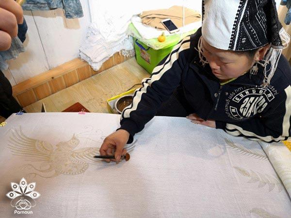 هنرمند چینی در حال ایجاد چاپ باتیک بر روی پارچه
